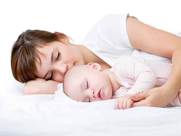 Baby im Bett zusammen mit der Mutter