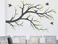 Pflanzen Wandtattoo Zweifarbiger Ast mit Vögeln über der Couch mit grünen Blättern